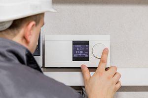 hvac technician inspecting thermostat