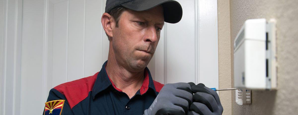hvac technician installing smart thermostat