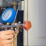 hvac technician using a manifold gauge