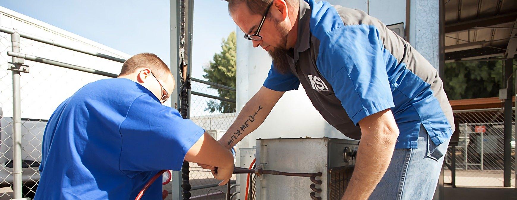 hvac technicians repairing unit