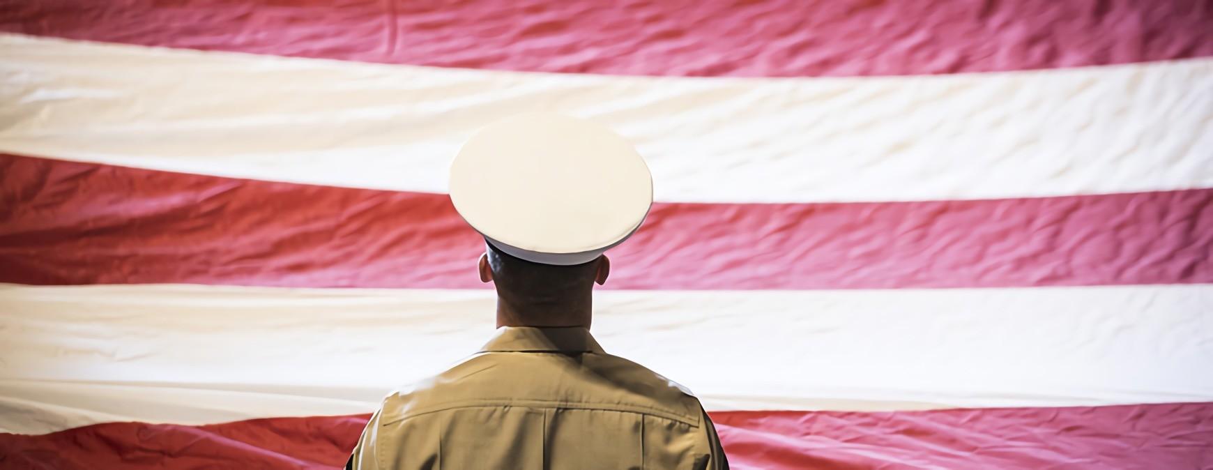 military veteran looking at us flag